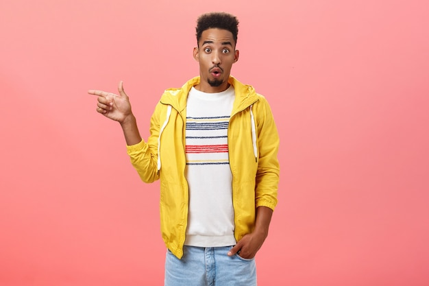 Studio shot of surprised impressed stylish african american male student in trendy yellow jacket folding lips in wow sound raising eyebrows from amazement pointing left questioned over pink wall