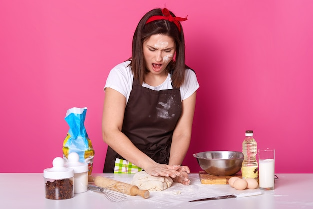 Studio shot of surprised woman wearing white t shirt and dirty apron with flour