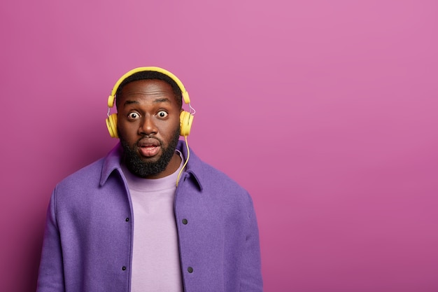 Studio shot of terrified black man stares at camera with bugged eyes, hears surprising news, wears modern stereo headphones