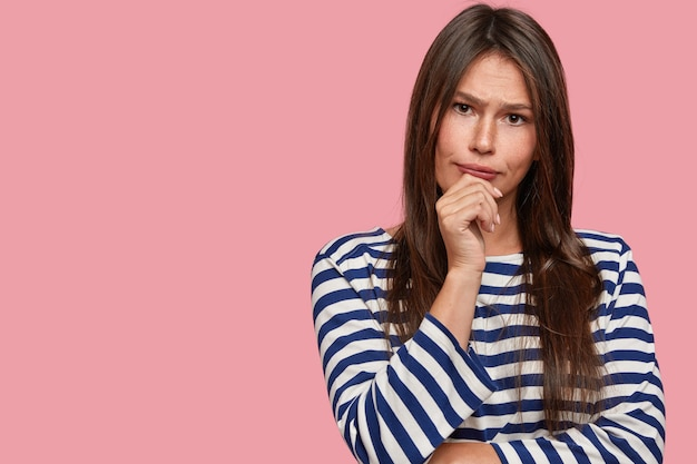 Studio shot of thoughtful woman holds chin, dressed in striped sailor sweater, looks seriously at camera