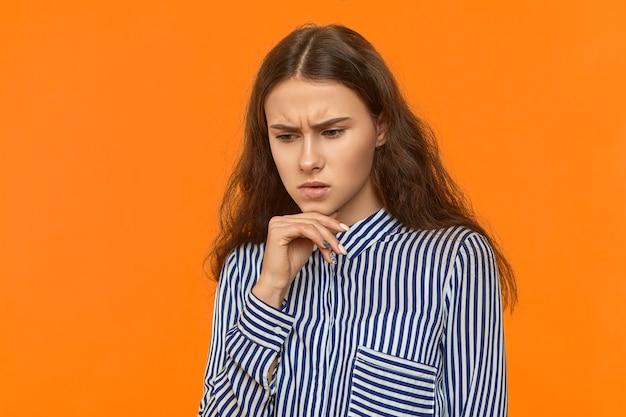 Lo studio ha sparato di giovane donna dai capelli scura premurosa che porta la mano alla moda della holding della camicia a strisce