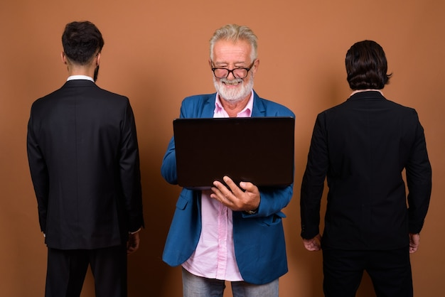 Studio shot of three multi ethnic bearded businessmen together against brown background