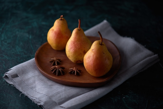 Studio shot of three pears and anise stars on a wooden plate