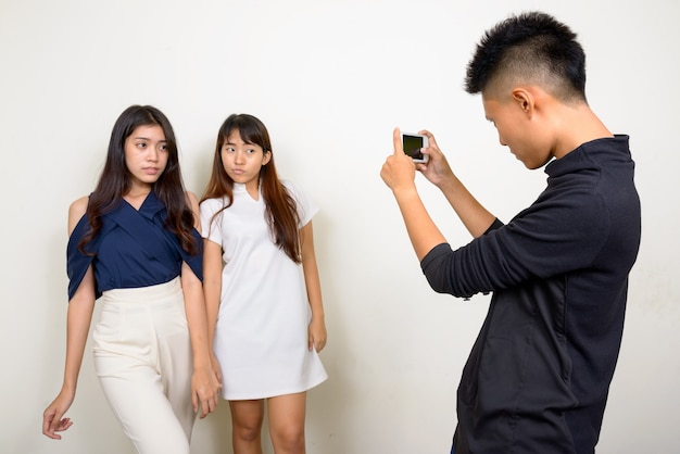 Studio shot of three young beautiful asian women as friends together against white background