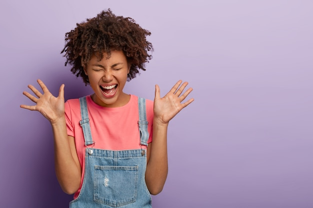 Studio shot of thrilled joyful woman with afro hairstyle laughs out from something funny, raises palms, feels very glad, has eyes shut, being very emotional, poses against purple background.