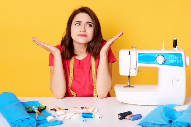 Studio shot of tsylist girl artisan seamstress sitting at white desk with sewing machine