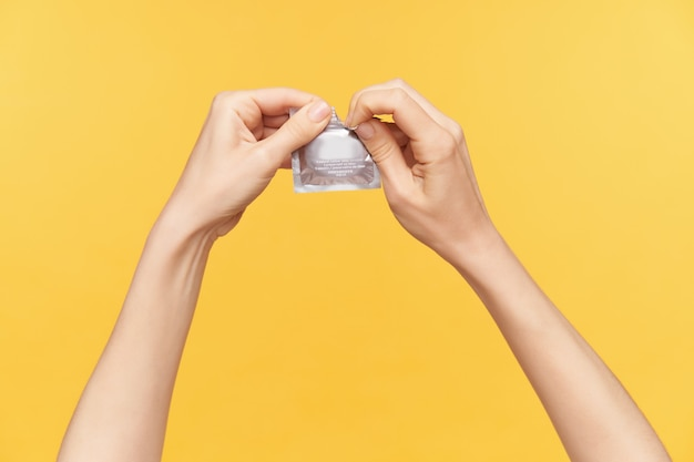 Studio shot of two raised hands being raised while opening pack with condom, going to have safe sex, isolated posing over orange background. human hands concept