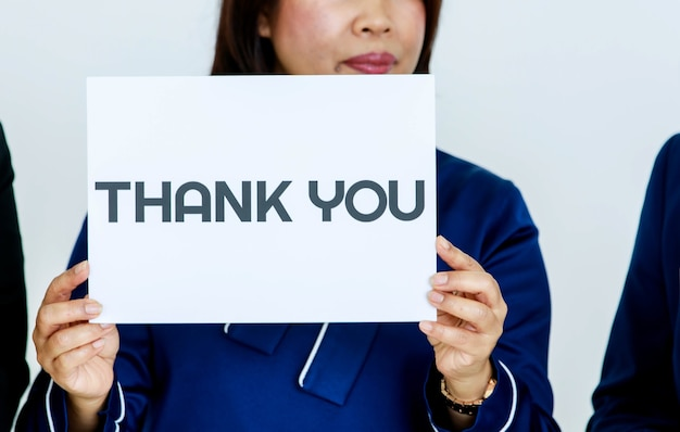 Studio shot of unrecognizable unidentified faceless female officer in business clothes holding thank you paper sign at chest showing appreciation to customers and colleagues on white background.