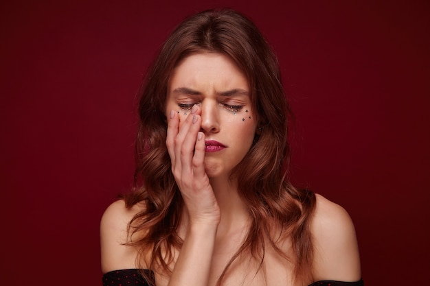 Studio shot of upset unhappy woman with brown wavy hair and festive makeup holding palm on her face and keeping eyes closed, almost going to cry while standing over claret background