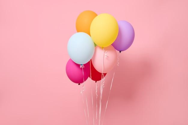 ピンク色の背景に隔離された、美しく明るくカラフルな気球の柔らかな影と広告用のコピースペースで撮影したスタジオ。誕生日パーティー、イベント、女性の日と夏のコンセプト