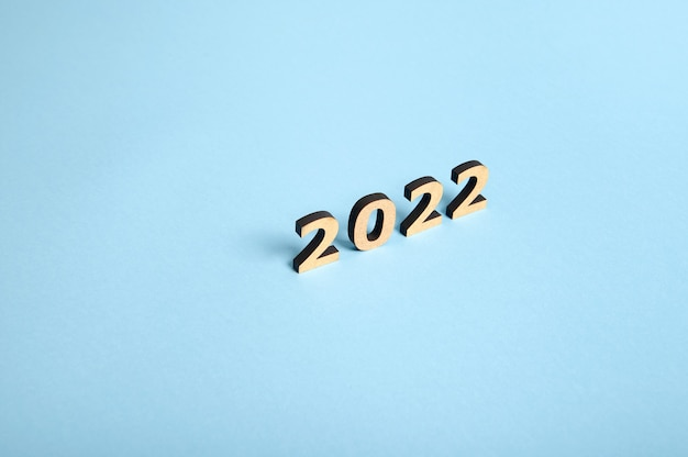 Studio shot with soft shadows falling on a blue surface of wooden numerals, symbolizing the new 2022 year on colored background with copy space for text or advertising. concepts