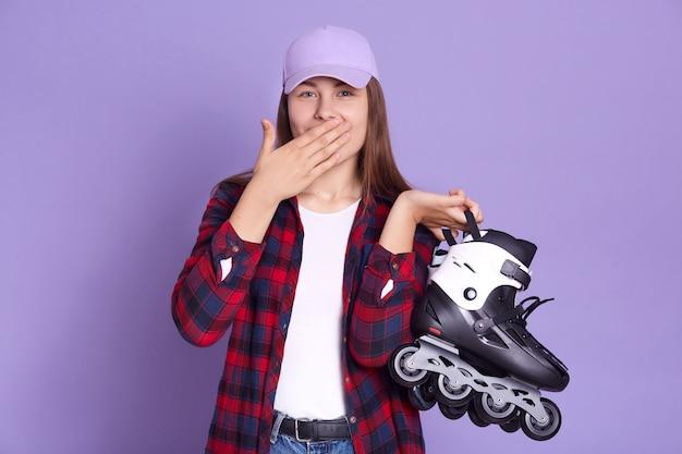Studio shot of woman wearing checkered shirt and cap