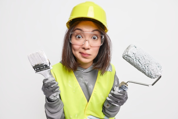 Studio shot of wondered woman industrial worker dressed in uniform holds paint brush and roller wears protective transparent glasses helmet gloves involved in construction work inspects area