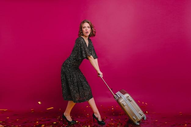 Studio shot di donna preoccupata in abito nero tenendo la valigia