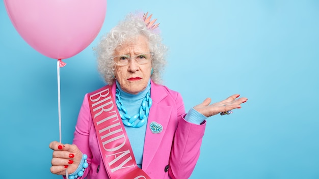 Studio shot of wrinkled grey haired elderly woman raises palms looks seriously, dressed in festive clothes holds inflated balloon celebrates birthday