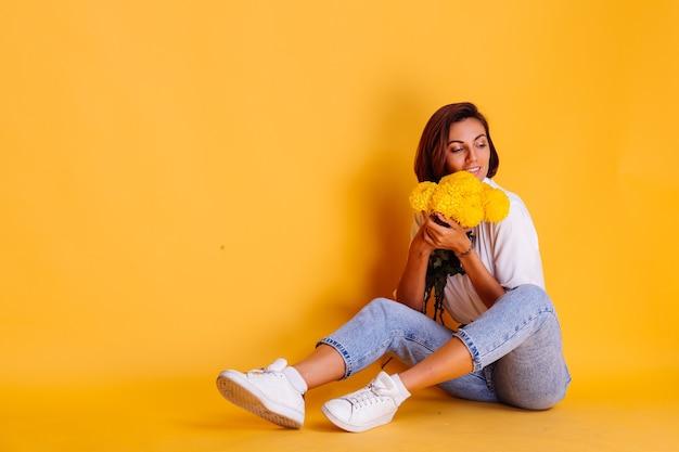 Studio girato su sfondo giallo felice indoeuropea donna capelli corti indossando abiti casual, camicia bianca e pantaloni in denim azienda bouquet di astri gialli