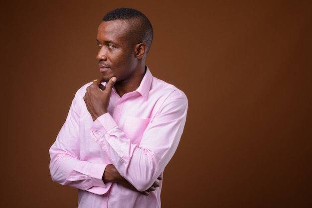 Studio shot of young african businessman against brown background