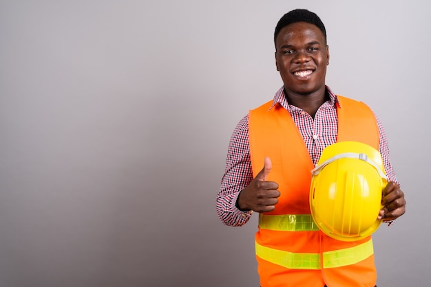 Studio shot of young african man construction worker against white background