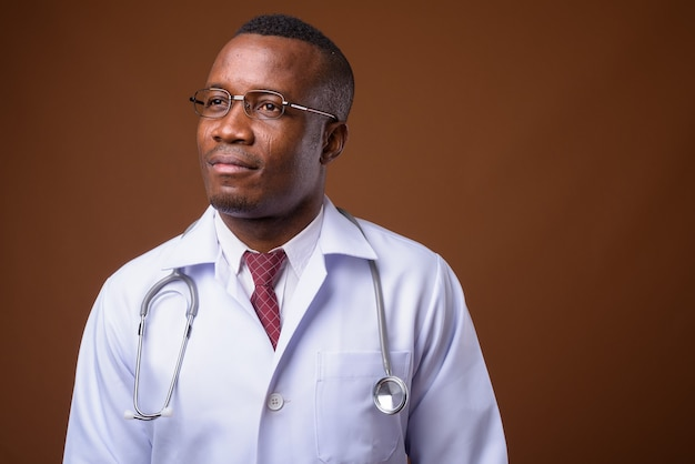 Studio shot of young african man doctor against brown background