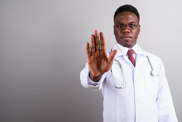 Studio shot of young african man doctor wearing eyeglasses against white background