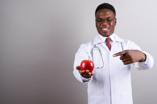 Studio shot of young african man doctor wearing eyeglasses while holding red apple against white background