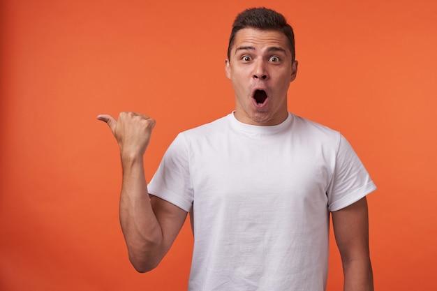 Studio shot di giovane agitato a pelo corto maschio vestito con t-shirt bianca sfogliare da parte e guardando emotivamente la fotocamera con la bocca aperta, in posa su sfondo arancione