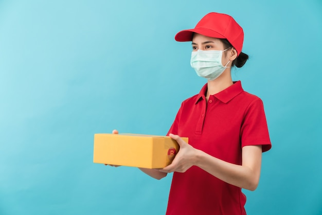 Studio shot of young asian woman in red cap shirt uniform wearing face mask and hand holding cardboard boxes on light blue background, delivery employee for service quarantine pandemic virus.