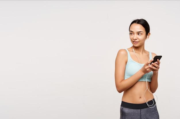 Colpo dello studio di giovane femmina castana attraente in buona forma fisica che tiene smartphone mentre ascolta la musica con i suoi auricolari, isolato sopra il muro bianco