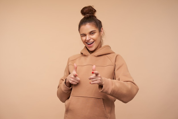 Studio shot of young attractive brunette woman with bun hairstyle winking happily while showing at front with raised hands, isolated over beige wall