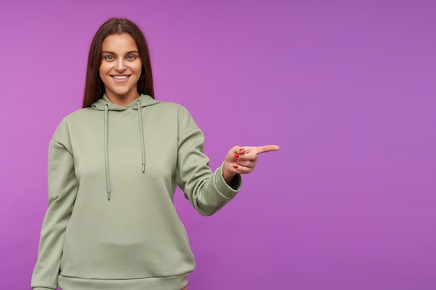 Studio shot of young attractive long haired brunette woman with red manicure looking happily at front while pointing aside with index finger, posing over purple wall