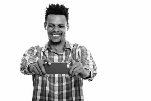 Studio shot of young bearded african businessman with afro hair isolated against white background in black and white
