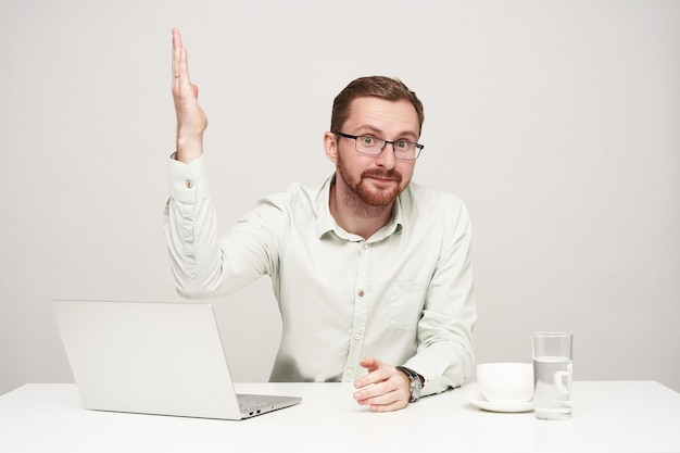 Studio shot of young bearded guy dressed in formal clothes keeping his lips folded while looking at camera and raising up hand, sitting over white background