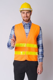 Studio shot of young bearded man construction worker against white