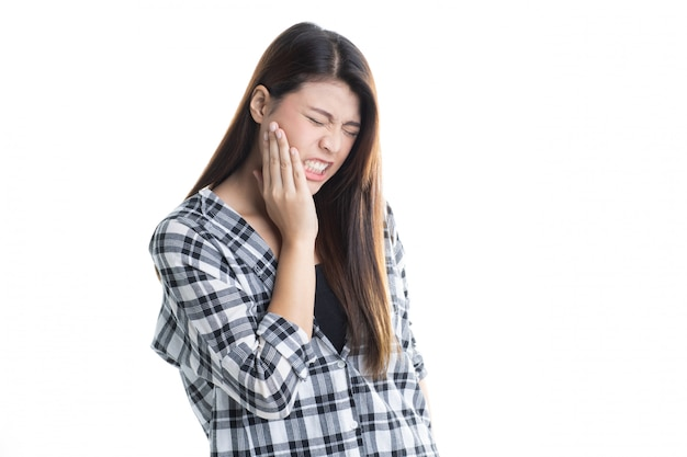Studio shot of young beautiful asian girl suffering with toothache isolated