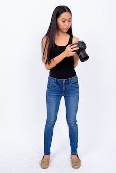 Studio shot of young beautiful asian woman against white background