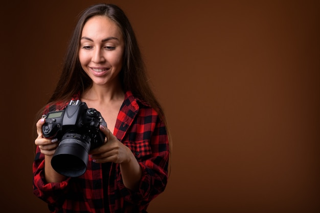 Studio shot of young beautiful woman with camera against brown background