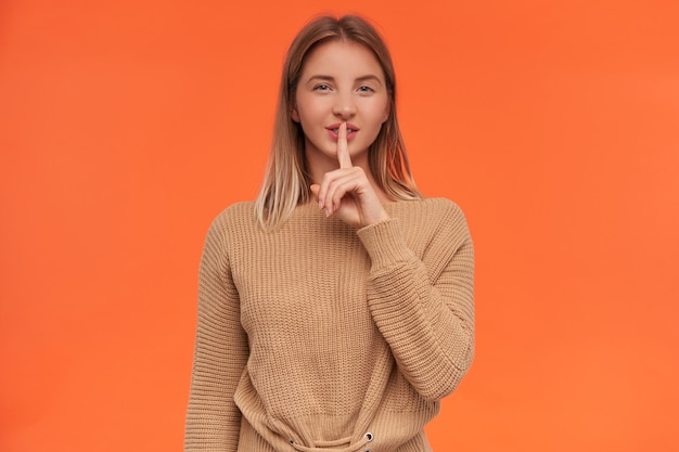 Studio shot of young blonde woman with short haircut keeping forefinger on her lips while asking to keep her secret and smiling cunningly, isolated over orange wall
