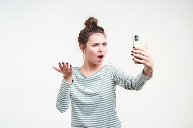 Studio shot di giovani dai capelli castani indignata signora che alza perplesso il suo palmo e le sopracciglia accigliate pur avendo conversazione telefonica emotiva, in piedi sopra il muro bianco
