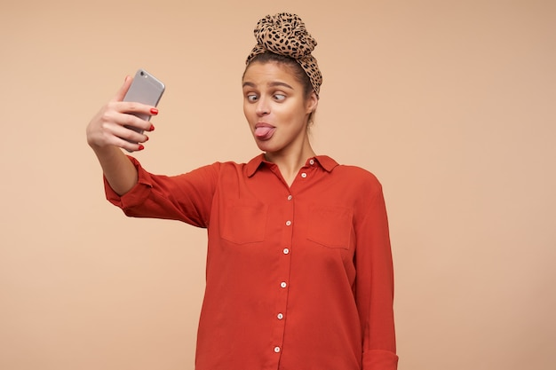 Studio shot of young brunette woman showing cheerfully her tongue and making funny faces while taking shot of herself, standing over beige wall