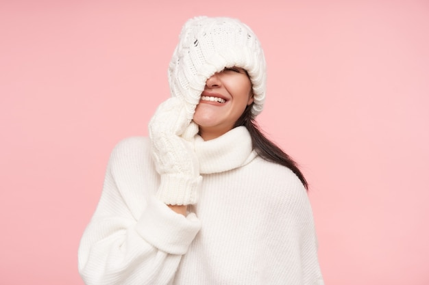 Studio shot of young cheerful brunette woman with loose hair taking off her hat and smiling happily while standing over pink wall in white cosy clothes