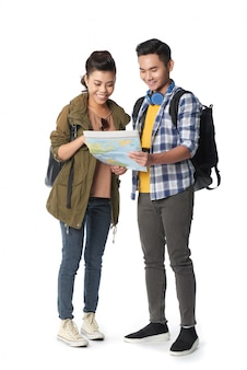 Studio shot of young couple with backpacks navigating the map against white background