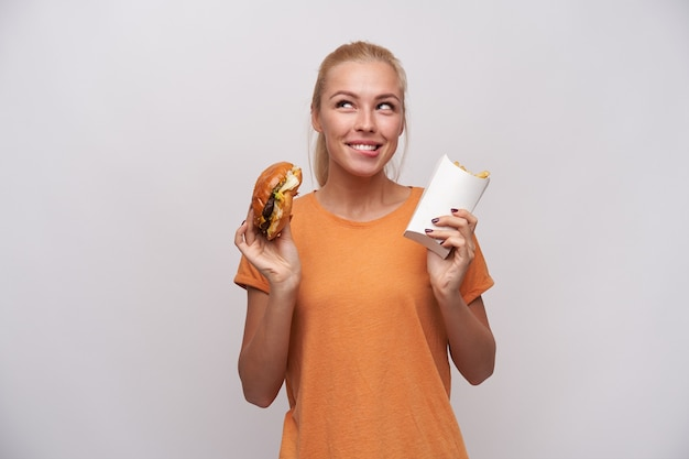 Studio shot of young delighted blonde female with casual hairstyle keeping hamburger and french fries in her hands and looking cheerfully aside, biting underlip and foretasting delicious dinner