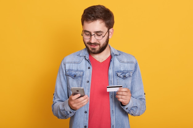 Studio shot of young european bearded man holding credit card and smartphone, standing with calm facial expression over yellow