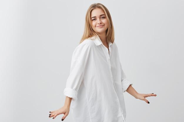 Lo studio sparato di giovani pantaloni a vita bassa femminili europei con capelli biondi si è vestito in camicia bianca di grande misura che posa all'interno alla parete in bianco. ragazza graziosa con l'espressione piacevole del fronte che sorride e che posa sulla macchina fotografica.