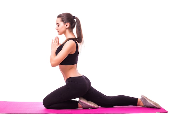 Studio shot of a young fit woman doing yoga exercises isolated on white background