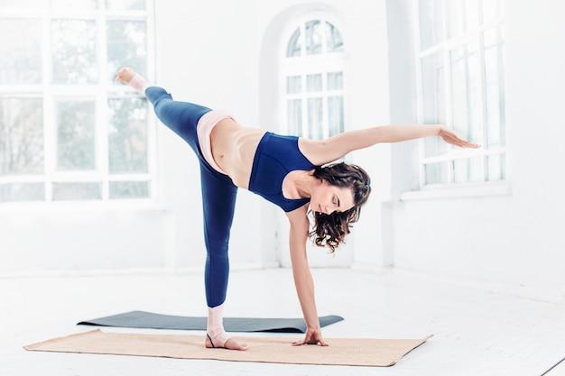 Il colpo dello studio di una donna adatta dei giovani che fa l'yoga si esercita su spazio bianco