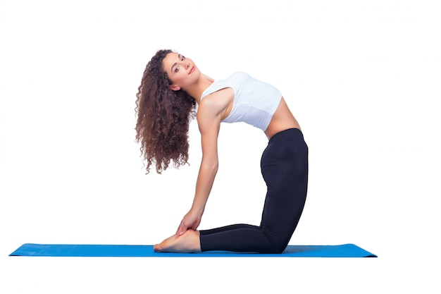 Studio shot of a young fit woman doing yoga exercises.