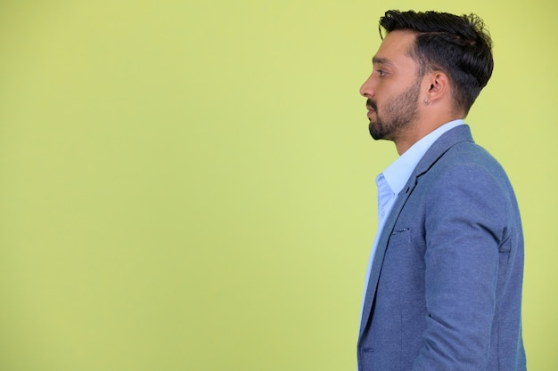 Studio shot of young handsome bearded persian businessman in suit against chroma key with green background
