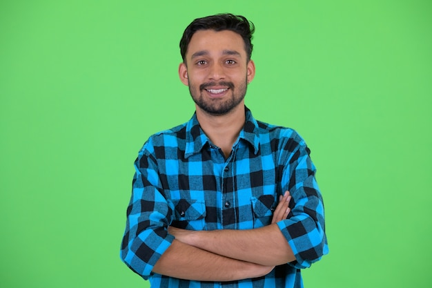 Studio shot of young handsome bearded persian hipster man against chroma key with green background