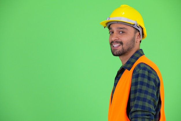 Studio shot of young handsome bearded persian man construction worker against chroma key with green background